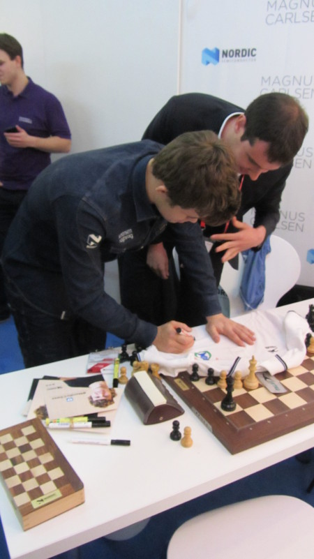Magnus Carlsen firmando un polo del Club Reverté